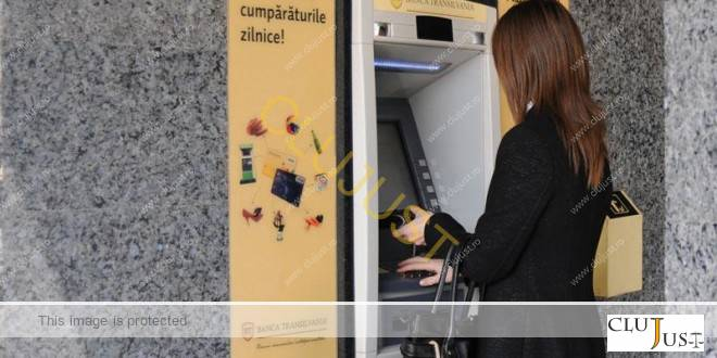 femeie scoate bani bancomat